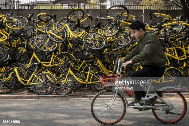 A commuter rides past worker piles of damaged and derelict bikes from the ride share company Ofo at a makeshift repair depot for the company where...