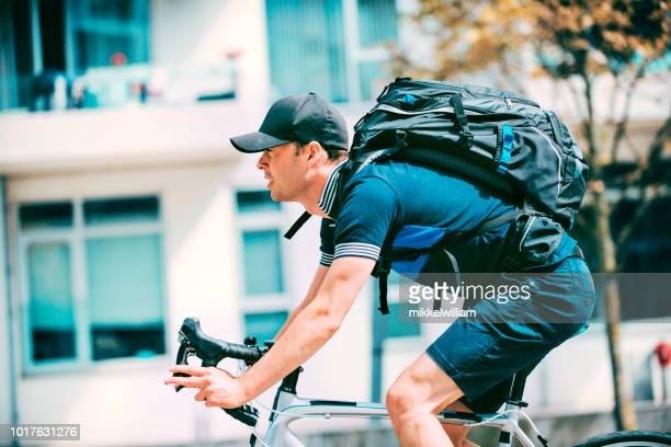 Commuter rides racing bicycle to work while wearing backpack