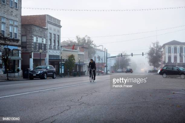 commuter riding bike rides towards camera on small town square - town stock pictures, royalty-free photos & images