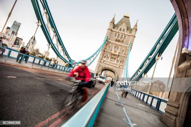 commuter riding fast on tower bridge in london - tower bridge stock photos and pictures
