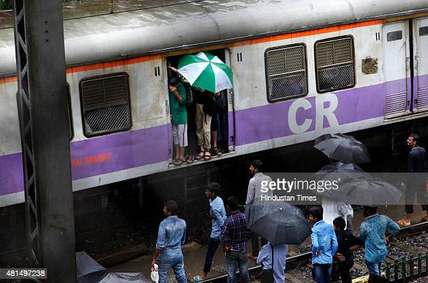 A commuter seen using umbrella to shield himself from rain while traveling in train on July 21 2015 in Mumbai India Heavy rains after the month long...