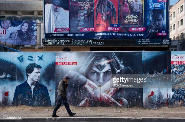 A commuter seen walking past large blockbuster movie posters