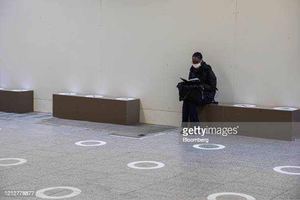 A commuter sits near social distancing floor markers at Gare Montparnasse railway station in Paris France on Tuesday May 12 2020 The Paris metro...