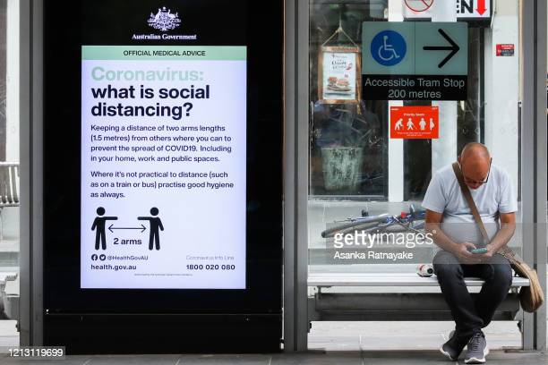 Commuter sits on a tram bench next to an LCD screen with an Australian Government directive regarding Coronavirus and social distancing on March 18,...