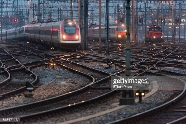 commuter train approaching busy railway track field at twilight - rail transportation stock pictures, royalty-free photos & images