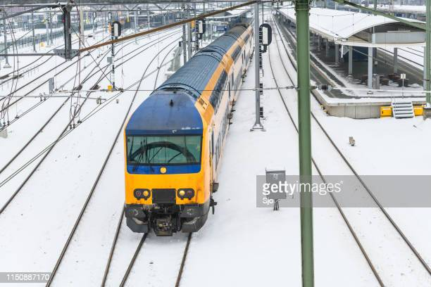 NS commuter train driving through the snow in winter
