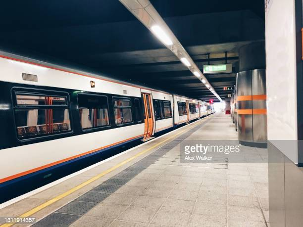 commuter train in covered station platform - station stock pictures, royalty-free photos & images
