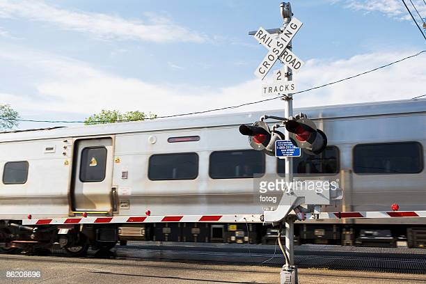 Commuter train moving through railroad crossing