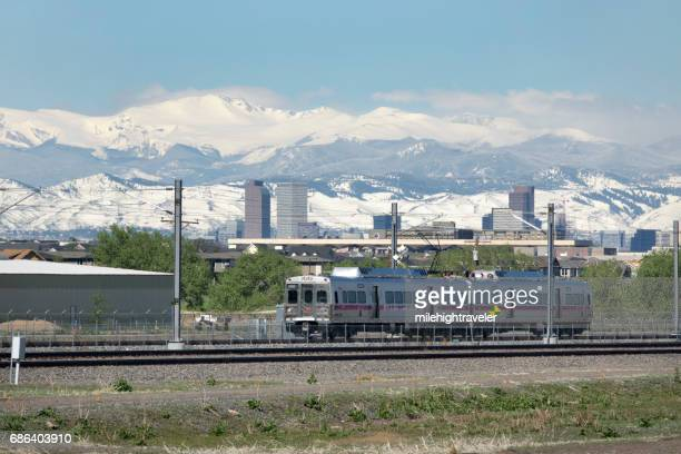 commuter train rolls past downtown denver snowy mount evans colorado rockies - front range mountain range stock pictures, royalty-free photos & images