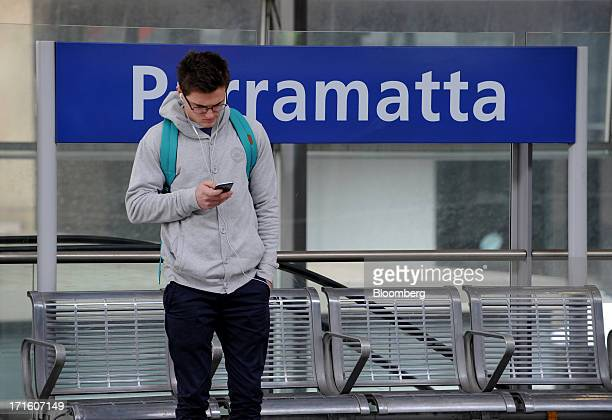 A commuter uses a mobile device as he stands on a platform at Parramatta train station in western Sydney Australia on Monday June 24 2013 Chris Bowen...