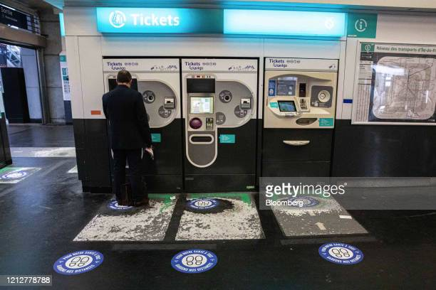 A commuter uses a ticket machine near social distancing floor markers at ChateletLesHalles metro station station in Paris France on Tuesday May 12...