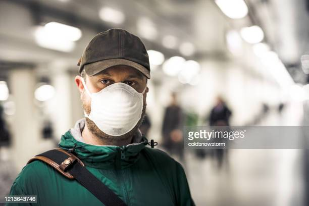 commuter waiting for train and wearing protective face mask in city railway station - mode of transport stock pictures, royalty-free photos & images