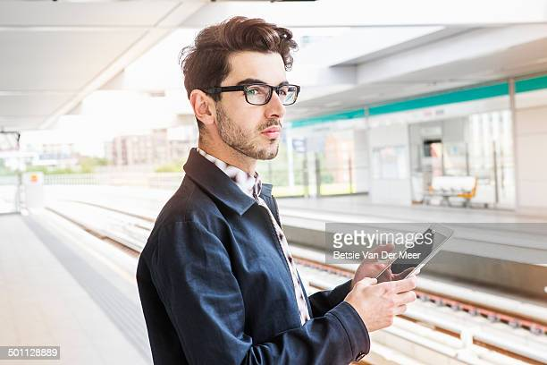 commuter waiting for train,holding digital device