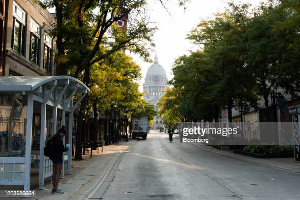A commuter waits at a bus stop near the Wisconsin State Capitol building in Madison Wisconsin US on Wednesday Sept 23 2020 A Wisconsin judge ruled...
