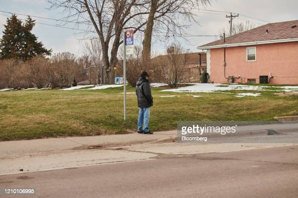 A commuter waits at a Sioux Area Metro bus stop in Sioux Falls South Dakota US on Wednesday April 15 2020 South Dakota Governor Kristi Noem has...