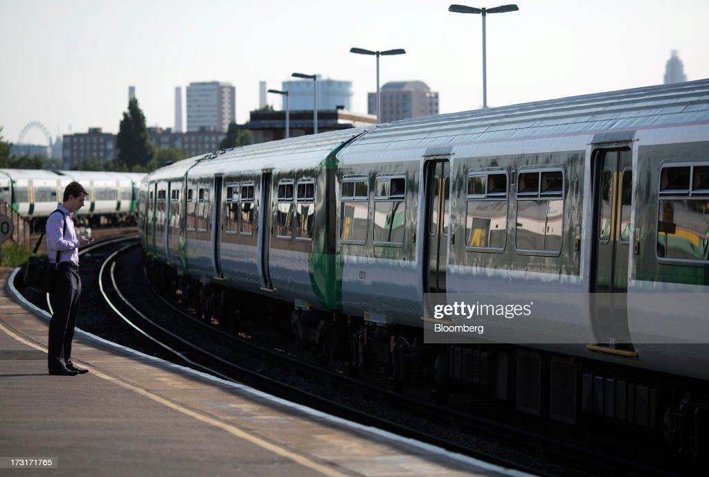 A commuter waits for a passenger train to arrive at Clapham Junction rail station in London, U.K., on Tuesday, July 9, 2013. U.K. Prime Minister David Cameron is committed to the building of a high-speed rail line linking London to northern England, his spokesman said as evidence mounts that all-party support for the project is fracturing. Photographer: Simon Dawson/Bloomberg via Getty Images
