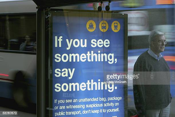 A commuter waits next to a terrorism awarness poster at a Sydney Bus station July 25 2005 in Sydney Australia The posters have been placed at train...