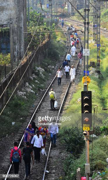 Commuter walk on the railway track as Dalit Protesters staged rail roko at Chembur Sation after the clashes between Dalit groups and supporters of...