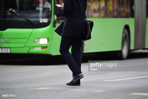 Commuter walking against green local bus, using phone