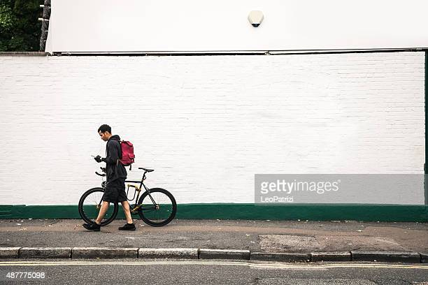 Commuter walking with bicycle in London streets
