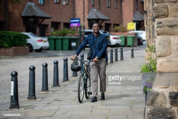 commuter walking with his bicycle - green blazer stock pictures, royalty-free photos & images