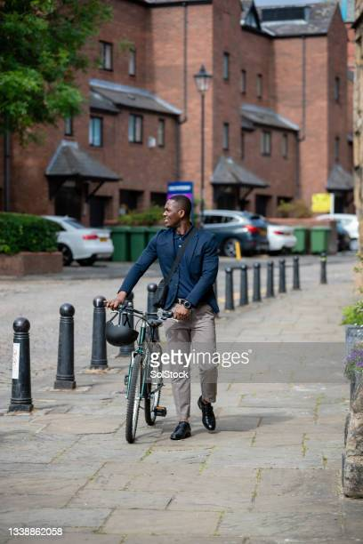 commuter walking with his bike - green blazer stock pictures, royalty-free photos & images