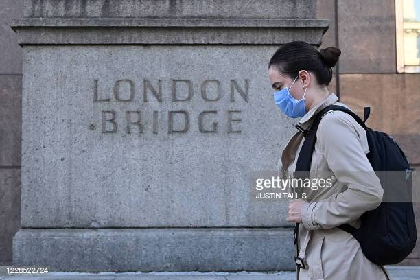 Commuter walks across London Bridge toward the City of London on September 15, 2020. - Britain's unemployment rate jumped above four percent in July...