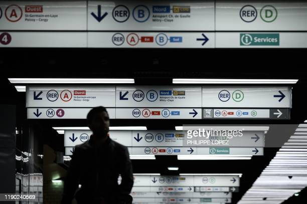 Commuter walks in a corridor of the Chatelet metro station on December 23, 2019 in Paris during a strike of public transports operators SNCF and RATP...