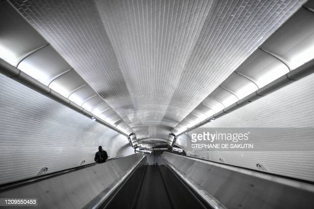 Commuter walks on a travelator at Chatelet-Les Halles metro station hub in Paris on April 8 on the twenty-third day of a lockdown in France to...