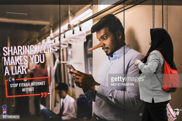 A commuter walks past an advertisement reading sharing a lie makes u a liar at a train station in downtown Kuala Lumpur on March 26 2018 The...
