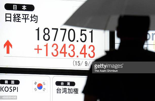 A commuter walks past an electric board displaying Nikkei 225 stock avarage on September 9 2015 in Tokyo Japan