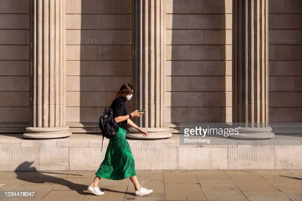 Commuter walks past the Bank of England in the City of London, U.K., on Thursday, Aug. 5, 2021. The Bank of England may move a step closer to...