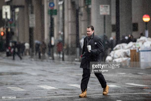 A commuter walks through a wintry mix of snow and sleet during the morning rush hour in the Financial District March 10 2017 in New York City A...