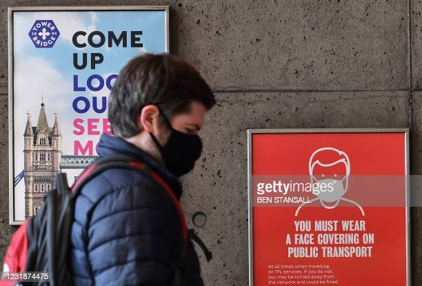 Commuter wearing a face covering passes a sign alerting travellers that due to Covid-19 face coverings are mandatory on public transport, as they...