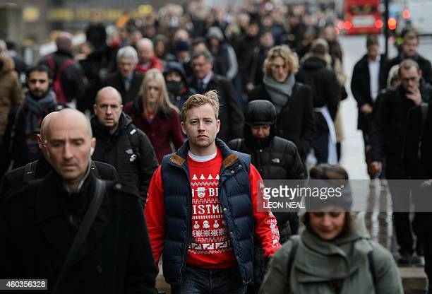 A commuter wearing a festive Christmas jumper crosses London Bridge during the morning rush hour on December 12 2014 Christmas jumpers once only...