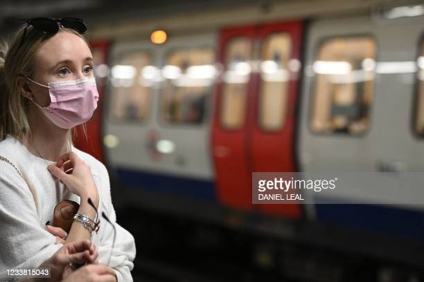 Commuter wearing a protective face covering to combat the spread of the coronavirus, travels on the Underground in central London on July 5, 2021. -...