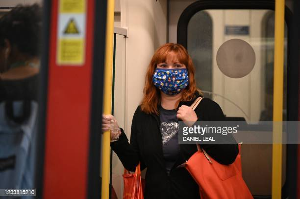 Commuter wearing a protective face covering to combat the spread of the coronavirus, travels on a Transport for London Underground train in central...