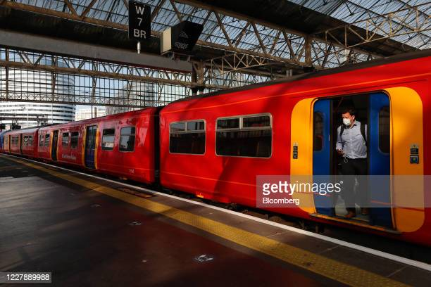 Commuter wearing a protective face mask disembarks from a train after arriving at London Waterloo railway station in London, U.K., on Monday, Aug. 3,...