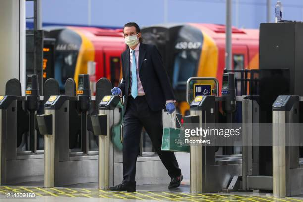 Commuter, wearing a protective face mask, passes through a ticket barrier at London Waterloo railway station in London, U.K., on Thursday, May 21,...