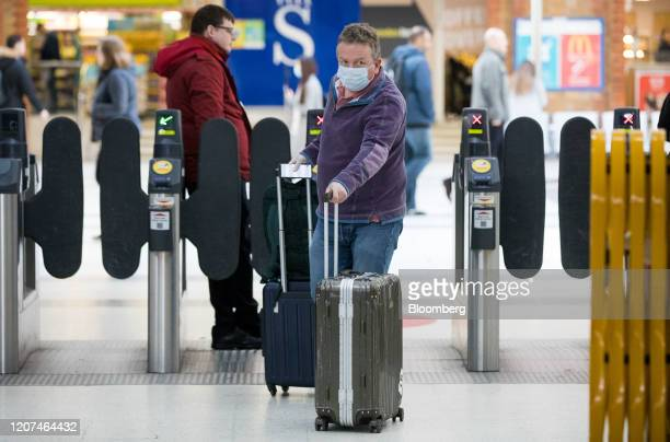 Commuter wearing a protective face mask pushes luggage through a ticket barrier at Liverpool Street station in London, U.K., on Tuesday, March 17,...