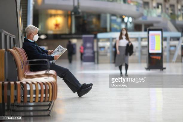 A commuter wearing a protective face mask reads a newspaper at London Waterloo railway station in London UK on Monday June 15 2020 British Prime...