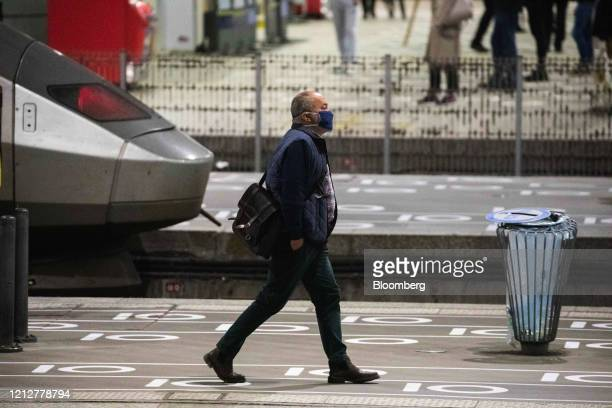 A commuter wearing a protective face mask walks on a platform after arriving at Gare Montparnasse railway station in Paris France on Tuesday May 12...