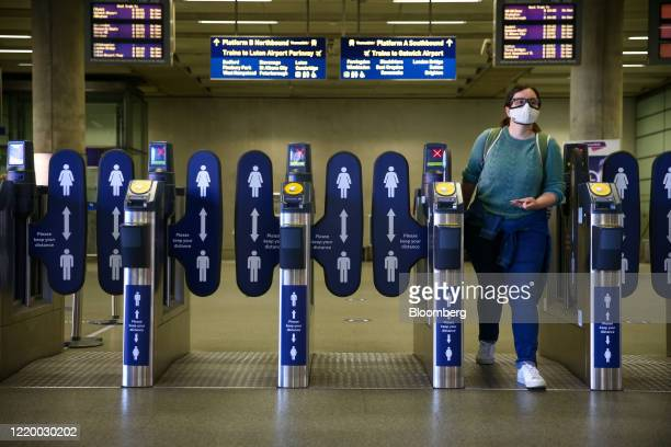 Commuter wearing a protective face mask walks through the ticket barriers at St. Pancras railway station in London, U.K., on Monday, June 15, 2020....