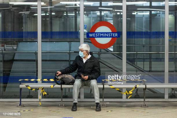 Commuter, wearing a protective face masks, sits on a bench next to social distancing measure at Westminster station on the London Underground in...