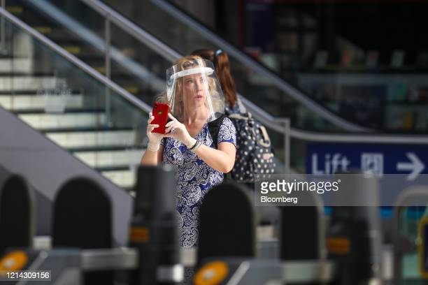 Commuter, wearing a protective face shield, walks along a concourse at London Waterloo railway station in London, U.K., on Thursday, May 21, 2020....