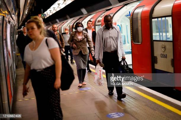 Commuter, wearing PPE as a precautionary measure against COVID-19, walks along the platform at a tube station in London on April 22 as Britain...