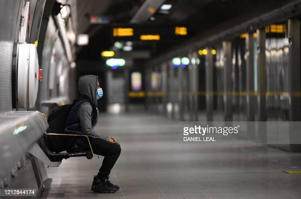 Commuter wearing PPE , including a face mask as a precautionary measure against COVID-19 waits to board a TfL Jubilee Line underground train at...