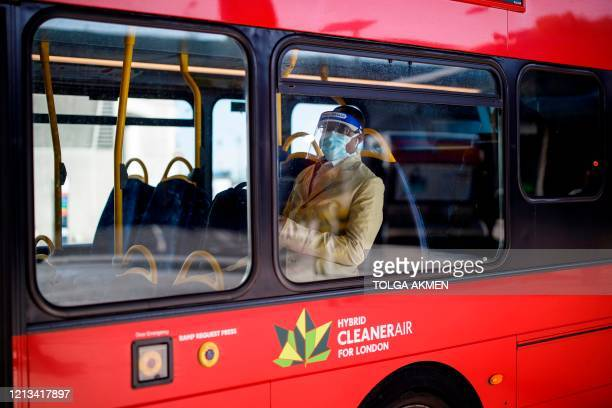 Commuter wearing PPE including a face mask as a precautionary measure against COVID-19, sits aboard a TFL red London bus at Vauxhall bus station in...
