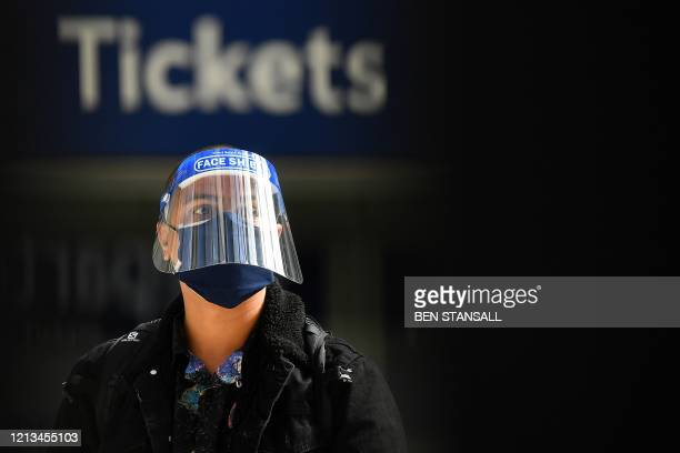 A commuter wearing PPE including a face shield and a face mask as a precautionary measure against COVID19 walks past a ticket booth at Waterloo Train...