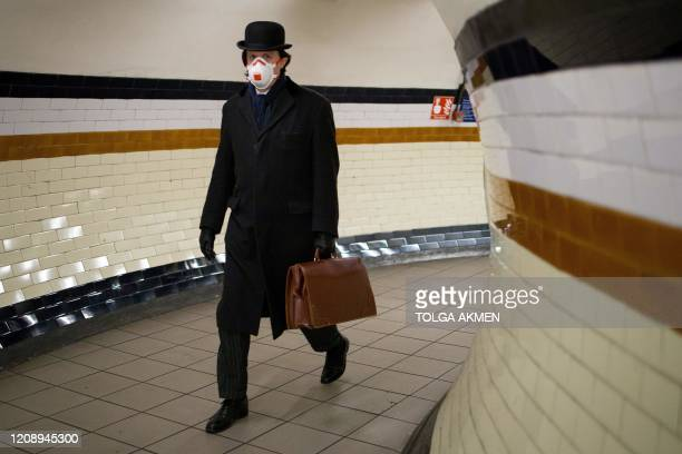 Commuter wears a face mask as a precautionary measure against the novel coronavirus COVID-19 as he walks at Lambeth North station to a Bakerloo line...